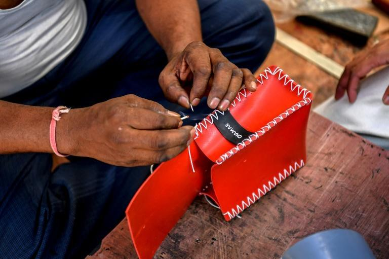 Artisan Sahdev Vishvnath Netake burns the stitches of a new recycled rubber bag