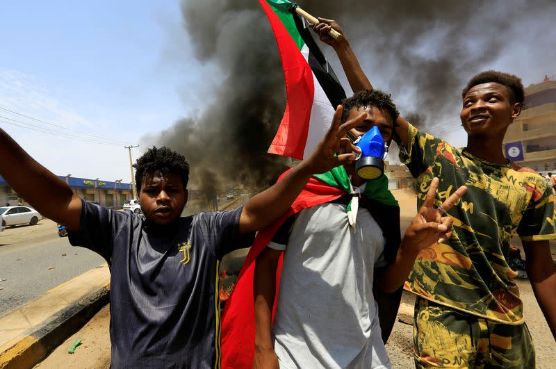 Civilians with the national flags gestures at a barricade as members of Sudanese pro-democracy group demonstrate on the anniversary of a major anti-military protest, as groups loyal to toppled leader Omar al-Bashir plan rival demonstrations in Khartoum