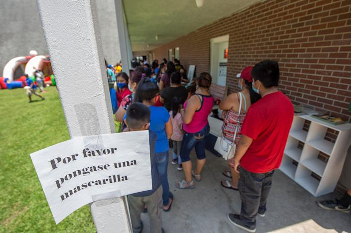 El Pueblo, a nonprofit specializing in immigration legal services, is ready with masks and hand sanitizer for people in line for school supplies during a school supply distribution at Trinity Mission Center in Forest, Miss., a Saturday, July 11, 2020. In August 2019, the Latino community was hard hit by ICE raids at local poultry plants. The event was hosted by El Pueblo in cooperation with Sugartown Riders Motorcycle Club from Kosciusko, Miss.