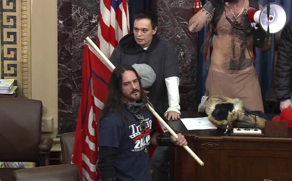 In this image from U.S. Capitol Police video, Paul Allard Hodgkins, 38, of Tampa, Fla., front, stands in the well on the floor of the U.S. Senate on Jan. 6, 2021, at the Capitol in Washington. Hodgkins, who carried a Trump 2020 flag while in the U.S. Senate during the Jan. 6 riot pleaded guilty on Wednesday, June 2, 2021, to a felony charge of obstructing an official proceeding. (U.S. Capitol Police via AP)