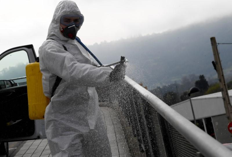 A member of the Military Emergency Unit (UME) sprays disinfectant to prevent the spread of the coronavirus disease (COVID-19) at Cabuenes Hospital during a 15-day state of emergency in Gijon