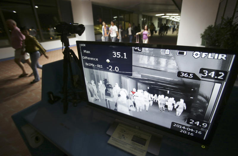"""FILE- In this Wednesday, April 16, 2014, file photo, passengers walk past a thermal scanner at the medical quarantine area at the arrival section of Manila's International Airport in Paranaque, south of Manila, Philippines. One expert says recent outbreaks of MERS in Saudi Arabia and the United Arab Emirates that led to more than 20 infections, many among health-care workers, """"have put us into uncharted territory."""" (AP Photo/Aaron Favila)"""