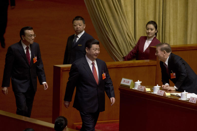 Chinese Communist Party chief and incoming-President Xi Jinping, center, walks in with Chinese incoming-Premier Li Keqiang to attend a plenary session of the National People's Congress where delegates are expected to elect Xi officially as president at the Great Hall of the People in Beijing, China, Thursday, March 14, 2013. (AP Photo/Ng Han Guan)