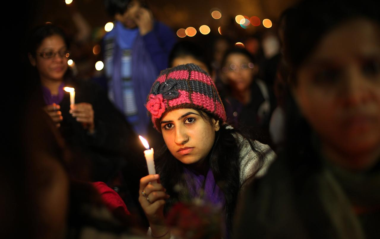 Indians participate in a candle lit vigil to mourn the death of a gang rape victim in New Delhi, India , Saturday, Dec. 29, 2012. Indian police charged six men with murder on Saturday, adding to accusations that they beat and gang-raped the woman on a New Delhi bus nearly two weeks ago in a case that shocked the country. The murder charges were laid after the woman died earlier Saturday in a Singapore hospital where she has been flown for treatment. (AP Photo/Altaf Qadri)
