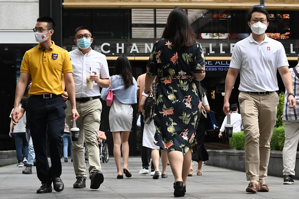 People walk during their lunch break in the financial business district of Raffles Place in Singapore on January 11, 2021. (Photo by Roslan RAHMAN / AFP) (Photo by ROSLAN RAHMAN/AFP via Getty Images)