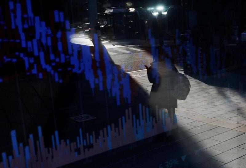 A woman using her mobile phone is reflected on an electric board showing exchange rates of various cryptocurrencies at Bithumb cryptocurrencies exchange in Seoul