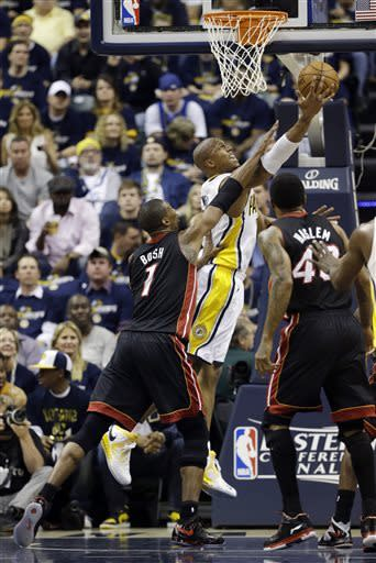Indiana Pacers' David West (21) puts up a shot against Miami Heat's Chris Bosh (1) and Udonis Haslem (40) during the first half of Game 3 of the NBA Eastern Conference basketball finals in Indianapolis, Sunday, May 26, 2013. (AP Photo/Nam H. Huh)