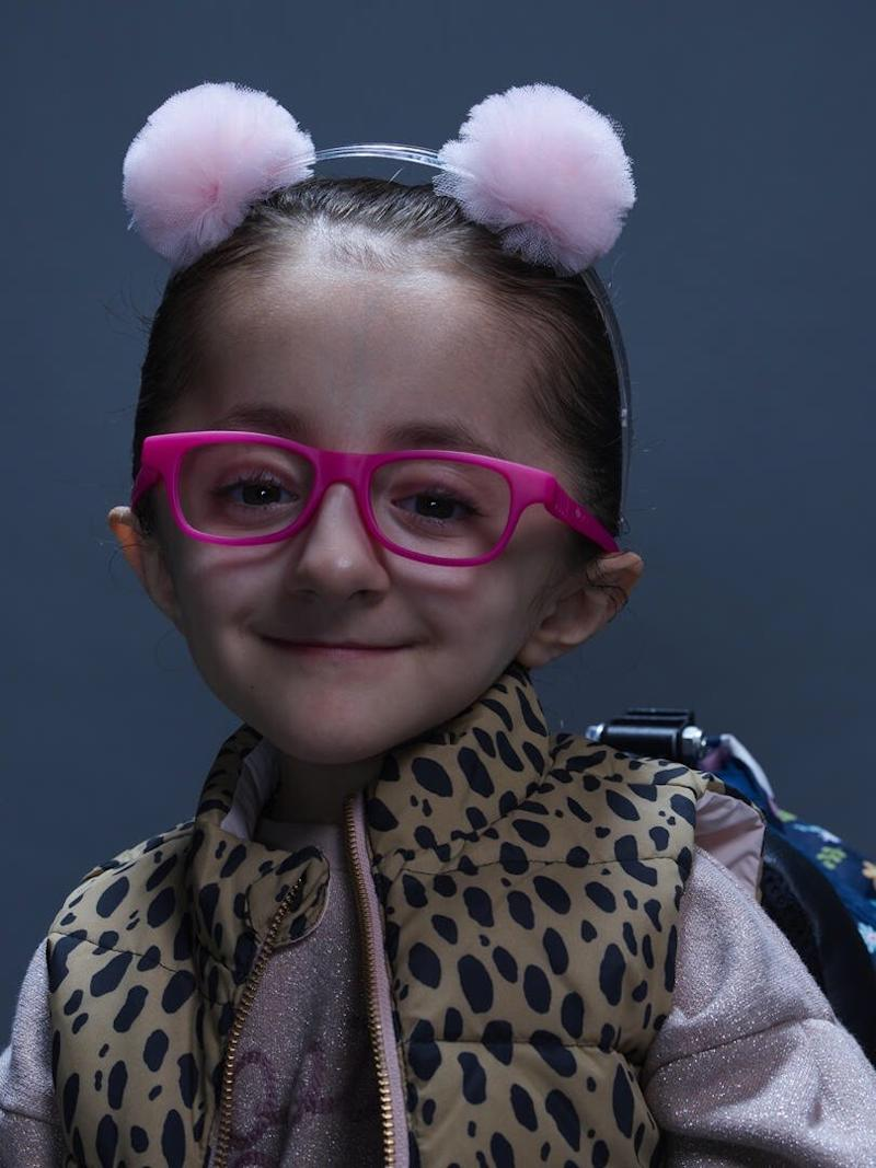 Sammi Haney, wearing cute pink glasses and a headband with pink ears on it.
