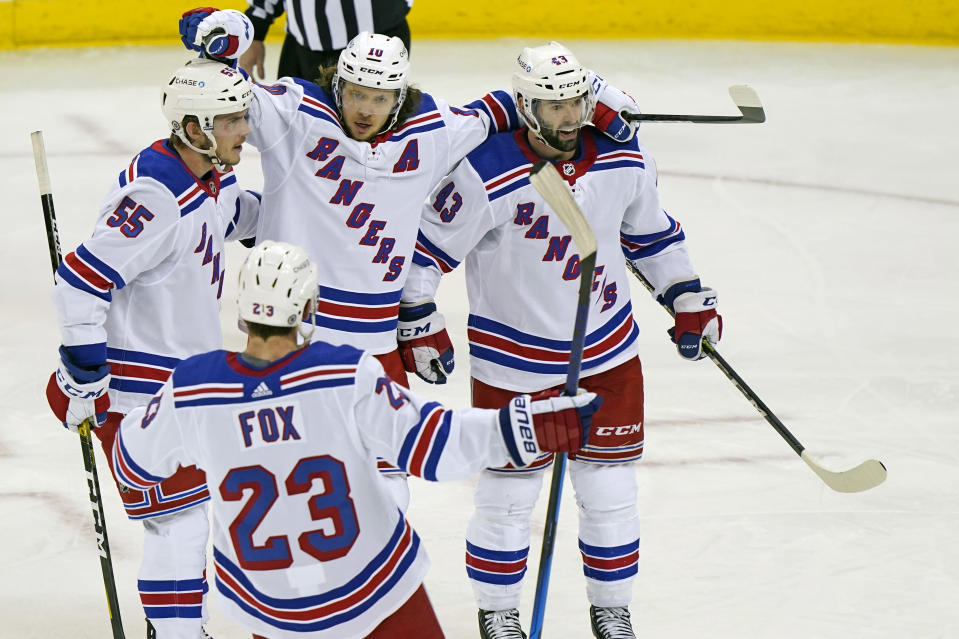 New York Rangers left wing Artemi Panarin (10) celebrates with defensemen Adam Fox (23), Ryan Lindgren (55) and center Colin Blackwell (43) after scoring the third period of an NHL hockey game against the New Jersey Devils, Tuesday, April 13, 2021, in Newark, N.J. (AP Photo/Kathy Willens)
