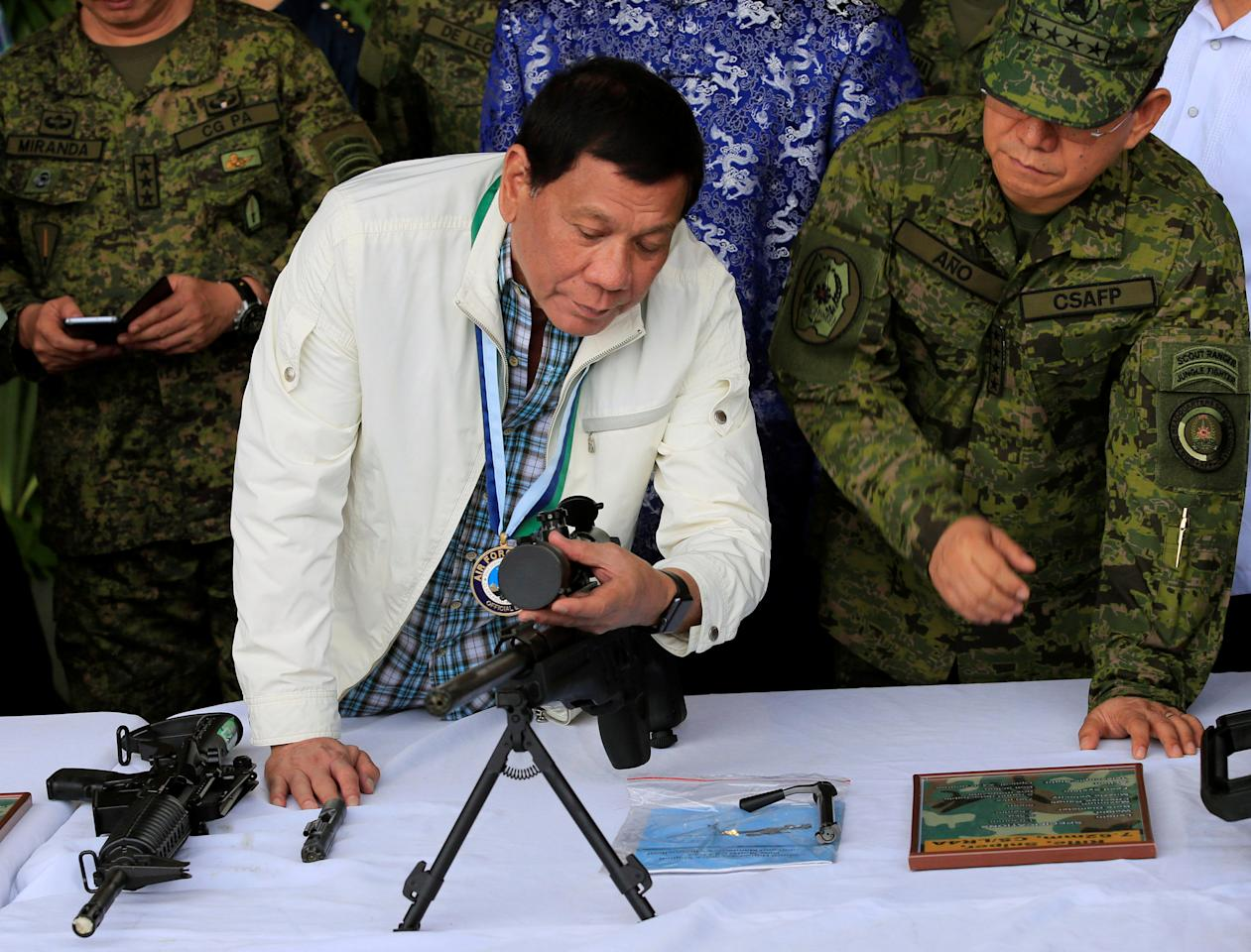 Philippine President Rodrigo Duterte adjusts the scope of a sniper rifle while Chief of Staff of the Armed Forces of the Philippines Lt. Gen. Eduardo Ano looks on at Clark Air Base, near Angeles City, Philippines June 28, 2017. REUTERS/Romeo Ranoco