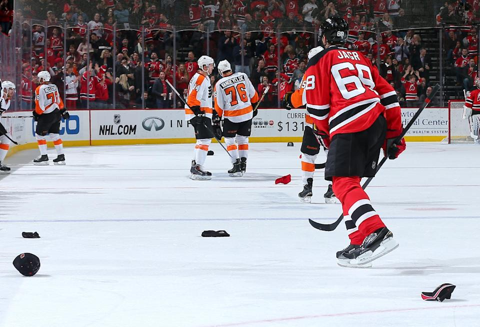 Jaromir Jagr of the New Jersey Devils skates toward the bench as fans throw hats onto the ice after Jagr scored a hat trick against the Philadelphia Flyers n January 3, 2015 at the Prudential Center in Newark, New Jersey (AFP Photo/Elsa)