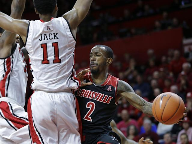Louisville guard Russ Smith (2) looks to pass around Rutgers forward Kadeem Jack (11) during the first half of an NCAA college basketball game in Piscataway, N.J., Saturday, Jan. 4, 2014. (AP Photo/Mel Evans)