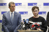Adam Hergenreder, right, responds to a question as Attorney Antonio Romanucci, listens after Romanucci announced the filing of a civil lawsuit against e-cigarette maker Juul, on behalf of Hergenreder, during a news conference Friday, Sept. 13, 2019, in Chicago. The lawsuit filed Friday in Lake County, Illinois, Circuit Court alleges Juul Labs, Inc., deliberately targeted young people through Instagram and other sites to suggest vaping can boost their social status. It also says Juul doesn't fully disclose their products contain dangerous chemicals. (AP Photo/Charles Rex Arbogast)