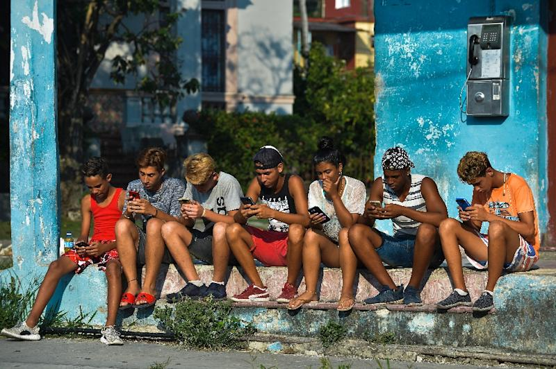 Young Cubans connect to the internet from their mobile phone in Havana, on June 6, 2019 (AFP Photo/YAMIL LAGE)