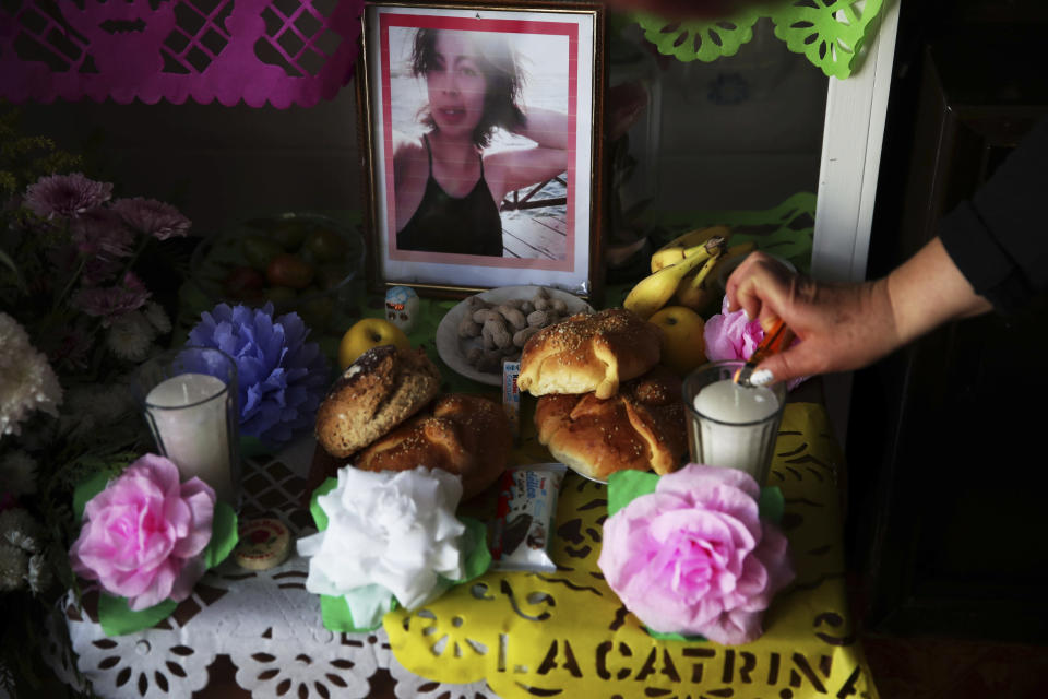 "Eulogia Herrera lights candles on a Day of the Dead altar featuring pictures of her daughter Mariana Luna Herrera who she said died of complications related to COVID-19, and who also had leukemia, at their home in Valle de Chalco on the outskirts of Mexico City, Friday, Oct. 30, 2020. Mexican families traditionally flock to local cemeteries to honor family members who died as part of the ""Day of the Dead"" holiday, every Nov. 1 and 2, but according to authorities cemeteries will be closed this year to help slow the spread of COVID-19. (AP Photo/Marco Ugarte)"