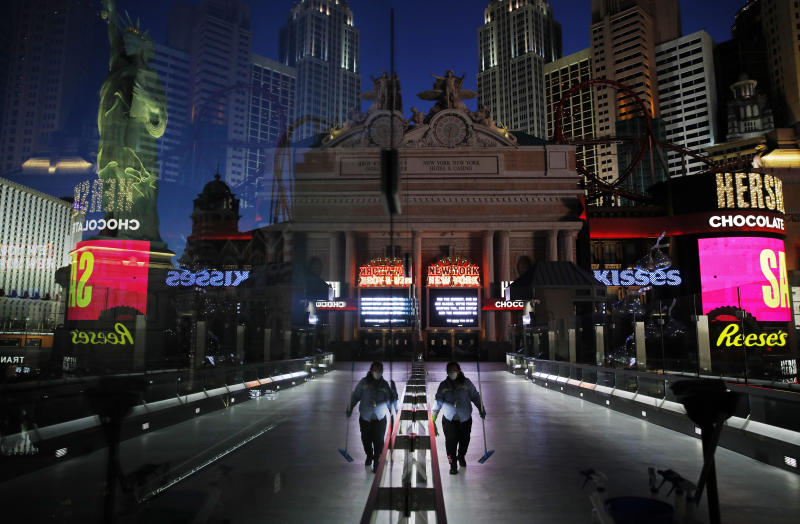 FILE - In this April 18, 2020, file photo, a lone worker wearing a mask cleans a pedestrian walkway devoid of the usual crowds as casinos and other business are shuttered due to the coronavirus outbreak in Las Vegas. Cards will be cut, dice will roll and jackpots jingle when casinos in Las Vegas and Nevada begin reopening at 12:01 a.m. on Thursday, June 4, 2020. There will be big splashes, even amid ongoing unrest, and big hopes for recovery from an unprecedented and expensive closure prompted by the coronavirus pandemic. (AP Photo/John Locher, File)