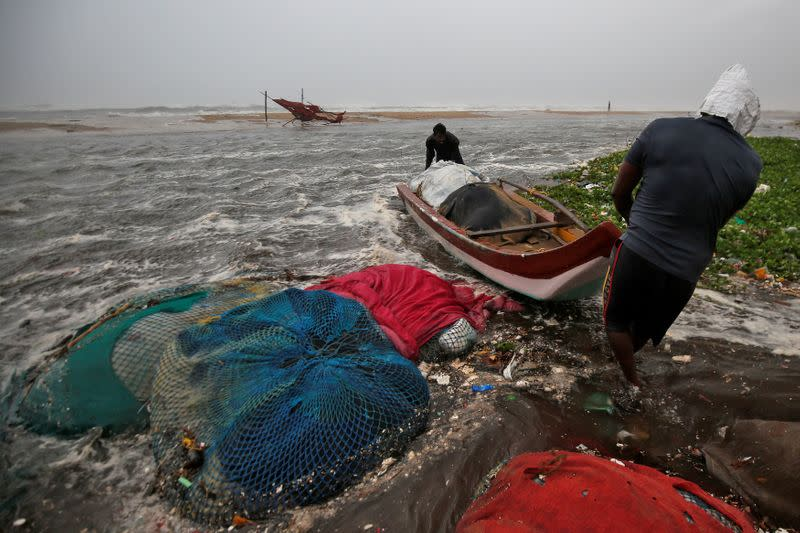 Fishermen move a fishing boat to a safer place along the shore before Cyclone Nivar's landfall, in Chennai