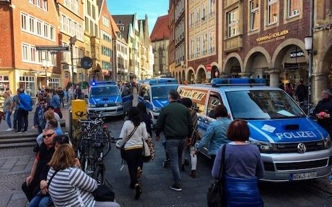 Police vans stand in downtown Muenster, Germany - Credit: AP