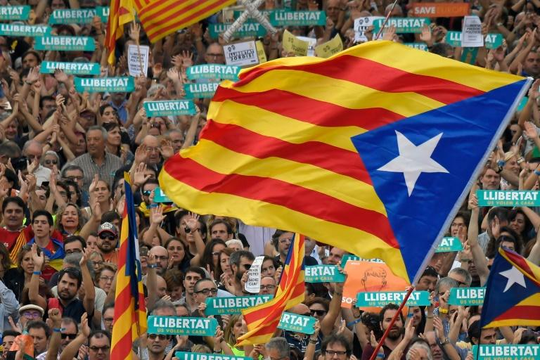Protesters wave pro-independence Catalan Estelada flags during a demonstration in Barcelona on October 21, 2017