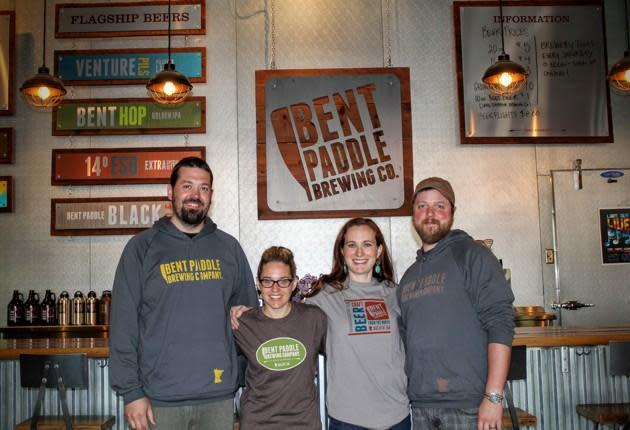 "Bryon Tonnis, Karen Tonnis, Laura Mullen, and Colin Mullen, the founders of <a href=""http://www.bentpaddlebrewing.com/"" rel=""nofollow noopener"" target=""_blank"" data-ylk=""slk:Bent Paddle Brewing"" class=""link rapid-noclick-resp"">Bent Paddle Brewing</a> company in Duluth, Minnesota. Their company's story illustrates the economic patterns that Jeff Alworth is describing. (James Fallows)"