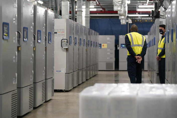 People stand near freezers used to store Pfizer-BioNtech's COVID-19 vaccine at a Pfizer manufacturing site, Friday, Feb. 19, 2021, in Portage, Mich. Efforts to vaccinate Americans against COVID-19 have been stymied by a series of winter storms and outages in parts of the country not used to extreme cold weather, and hobbled transportation hubs and highways. (AP Photo/Evan Vucci)