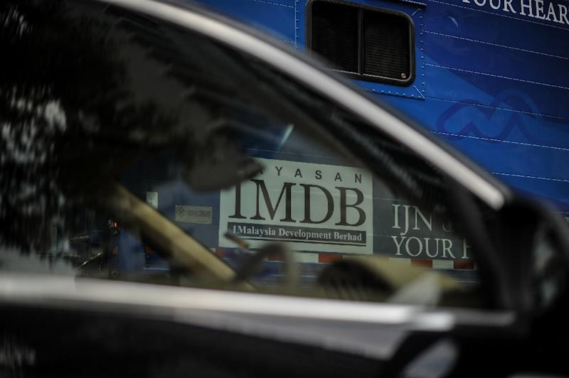 The 1 Malaysia Development Berhad (1MDB) logo is seen through the window of a car in Kuala Lumpur on March 14, 2016. (AFP Photo/MOHD RASFAN)