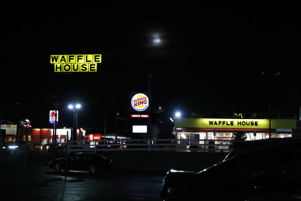 A Waffle House, Burger King, and Taco Bell are among the restaurants with lit signs seen along a road at night in Burlington, N.C., Monday, March 9, 2020. (AP Photo/Jacquelyn Martin)