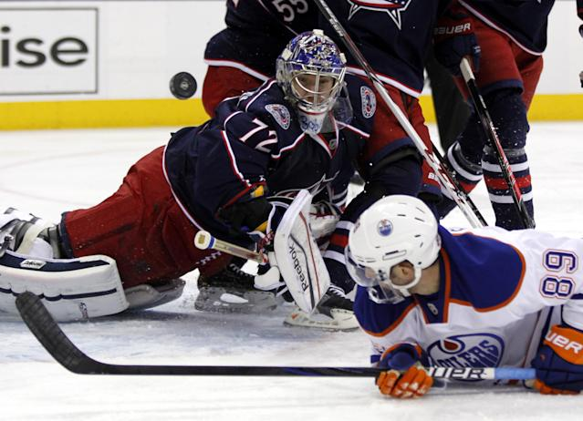 Columbus Blue Jackets goalie Sergi Bobrovsky, left, of Russia, stops a shot against Edmonton Oilers' Sam Gagner (89) in the first period of an NHL hockey game in Columbus, Ohio, Friday, Nov. 29, 2013. (AP Photo/Paul Vernon)