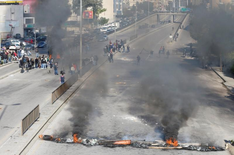 Protestors close a road with burning barricades during a protest over economic hardship and lack of new government in Beirut