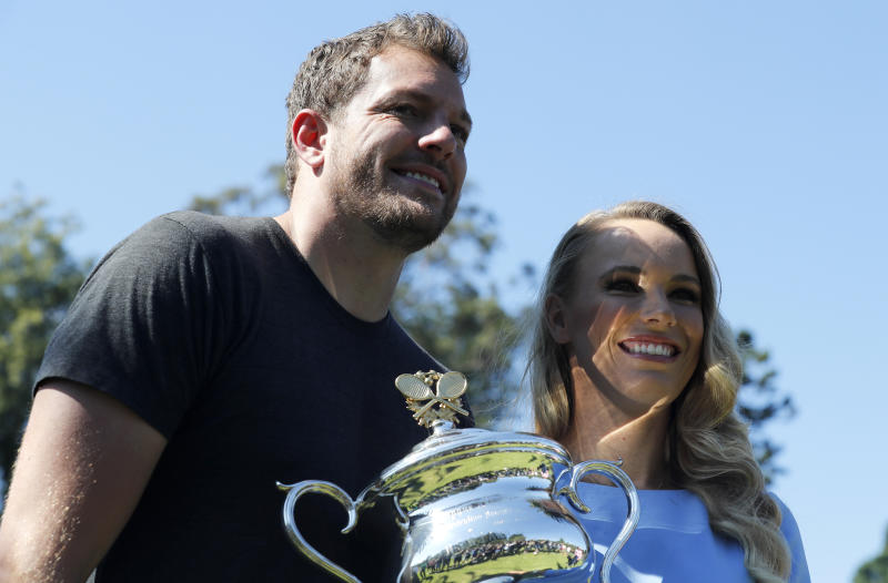 Denmark's Caroline Wozniacki and fiance' David Lee with her Australian Open trophy, the Daphne Akhurst Memorial Cup in the Royal Botanical Gardens in Melbourne, Australia, Sunday, Jan. 28, 2018. Wozniacki defeated Romania's Simona Halep 7-6, 3-6, 6-4 in Saturday's final.(AP Photo/Ng Han Guan)