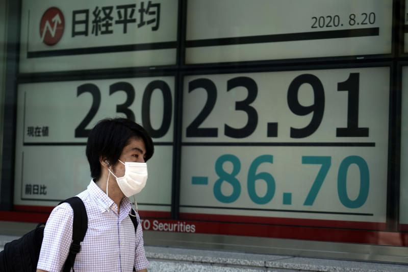 A man walks past an electronic stock board showing Japan's Nikkei 225 index at a securities firm in Tokyo Thursday, Aug. 20, 2020. Asian shares slipped Thursday after sobriety set in on Wall Street, and the U.S. Federal Reserve minutes laid out challenges for the economy amid the coronavirus pandemic. (AP Photo/Eugene Hoshiko)