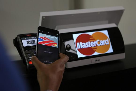 Card reader with the Mastercard logo, with a hand holding a mobile device over the reader.