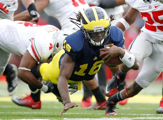 ANN ARBOR, MI - NOVEMBER 26: Denard Robinson #16 of the Michigan Wolverines dives for extra yards past C.J. Barnett #4 of the Ohio State Buckeyes at Michigan Stadium on November 26, 2011 in Ann Arbor, Michigan. Michigan won the game 40-34. (Photo by Gregory Shamus/Getty Images)