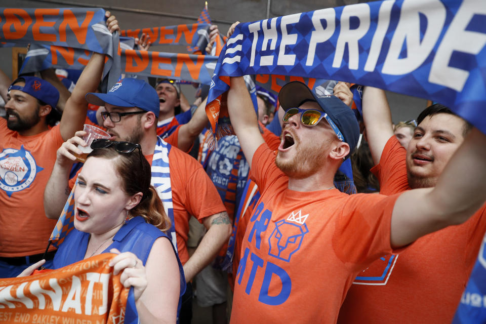 Fans cheer before speakers take the stage at an event to announce the addition of FC Cincinnati to Major League Soccer, Tuesday, May 29, 2018, at Rhinegeist Brewery in Cincinnati. FC Cincinnati has set attendance records in its three seasons in the United Soccer League and will get a soccer-only stadium in two years. The announcement on Tuesday brings MLS a step closer to its goal of a 28-team league. The latest round of expansion will bring it to 26 teams. (AP Photo/John Minchillo)