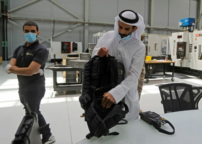 Ahmed Rashed Al-Moosafri (R), the director of Qatar's Barzan facility, shows an amphibious assault respirator device which contains the component now being used in a medical ventilator (AFP Photo/KARIM JAAFAR)