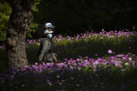 A woman wearing a face mask to protect against the coronavirus walks past blooming flowers at a public park in Beijing, Saturday, Oct. 24, 2020. With the outbreak of COVID-19 largely under control within China's borders, the routines of normal daily life have begun to return for its citizens. (AP Photo/Mark Schiefelbein)