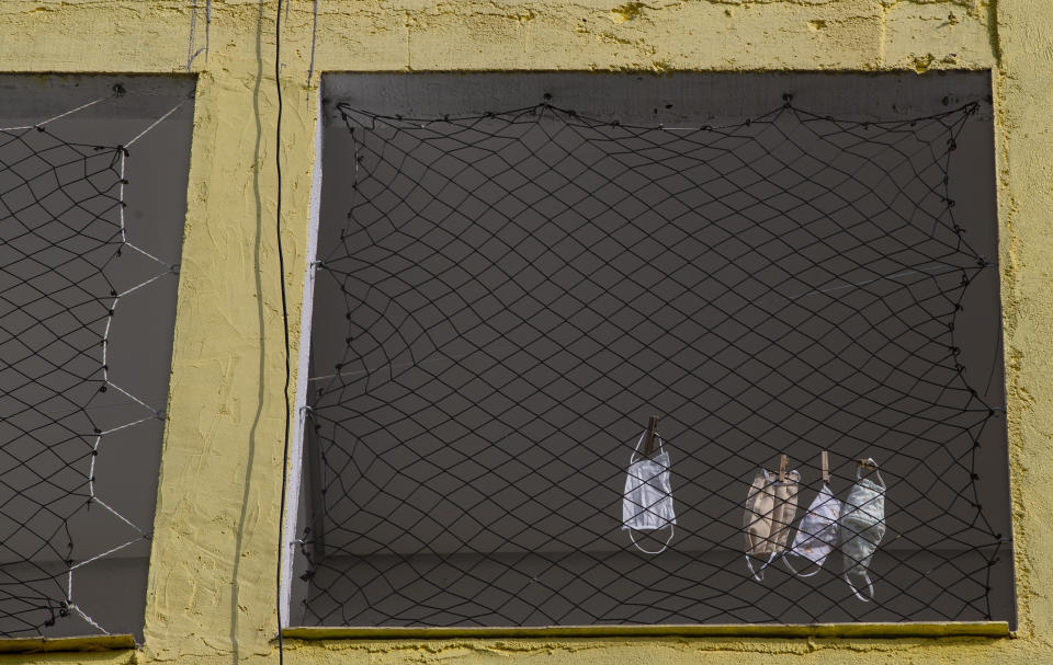 Masks hang to dry in a home's window in the Paraisopolis slum of Sao Paulo, Brazil, Wednesday, May 6, 2020. With over 100,000 residents, this community is one of the areas most affected by COVID-19 in Sao Paulo. (AP Photo/Andre Penner)