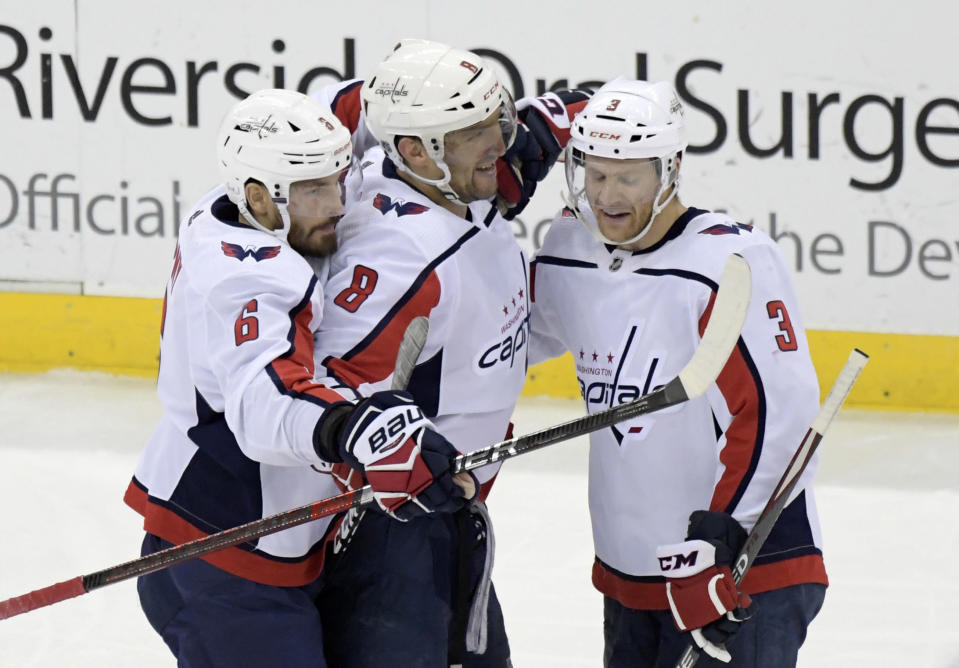 Washington Capitals left wing Alex Ovechkin (8) celebrates his 700th career goal with defenseman Michal Kempny (6) and defenseman Nick Jensen (3) during the third period of an NHL hockey game against the New Jersey Devils Saturday, Feb. 22, 2020, in Newark, N.J. (AP Photo/Bill Kostroun)