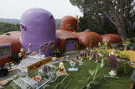 """FILE - In this Thursday, April 11, 2019, file photo, The Flintstone House is seen before a news conference with the owner and the home's original architect in Hillsborough, Calif. The San Francisco Bay Area suburb of Hillsborough is suing the owner of the house, saying that she installed dangerous steps, dinosaurs and other Flintstone-era figurines without necessary permits. In a yabba dabba dispute that pitted property rights against government rules that played out in international media, retired publishing mogul Florence Fang defended her colorful, bulbous-shaped house and its elaborate homage to """"The Flintstones"""" family, featuring Stone Age sculptures inspired by the 1960s cartoon, along with aliens and other oddities. (AP Photo/Eric Risberg, File)"""