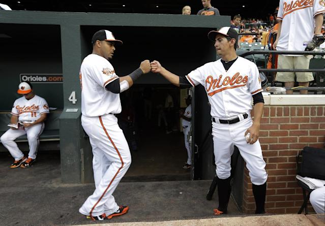 In this July 9, 2014 photo, Baltimore Orioles designated hitter Nelson Cruz, left, fist-bumps batboy Andrew Guinart in the dugout before a baseball game against the Washington Nationals in Baltimore. (AP Photo/Patrick Semansky)