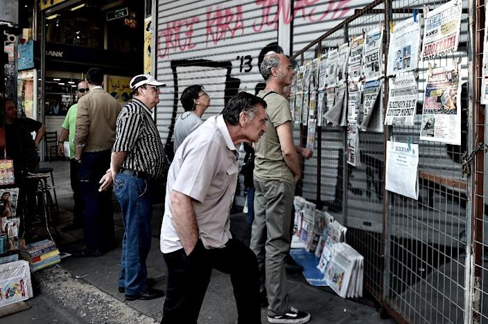 People read newspapers in central Athens on June 30, 2015 (AFP Photo/Aris Messinis)