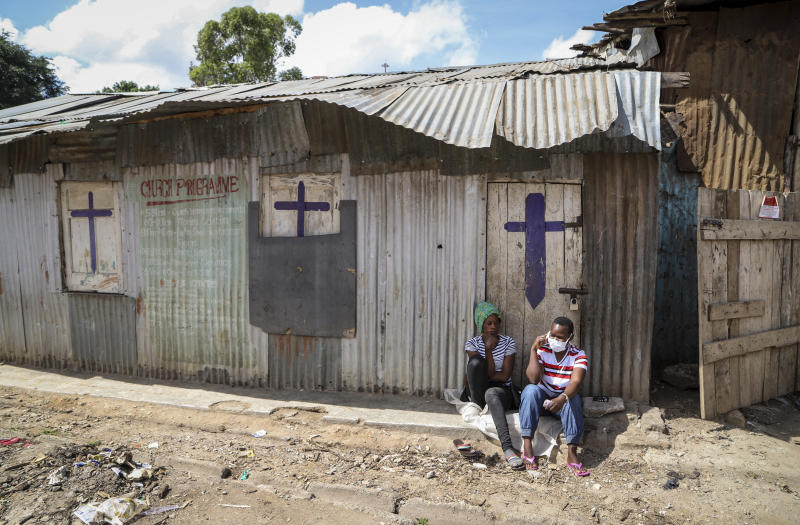 FILE - In this Sunday, April 12, 2020 file photo, two residents sit outside a closed church, after religious public services were stopped to limit the spread of the coronavirus, in the Mathare slum, or informal settlement, of Nairobi, Kenya. The COVID-19 pandemic is testing the patience of some religious leaders across Africa who worry they will lose followers, and funding, as restrictions on gatherings continue. (AP Photo/Patrick Ngugi, File)