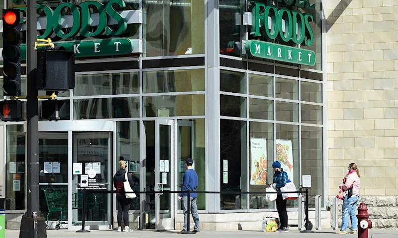 Shoppers wait in line at a Whole Foods grocery store in Minneapolis, Minnesota, 21 March 2020.
