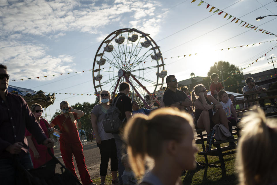 People watch a pig race at the Mississippi State Fair, Wednesday, Oct. 7, 2020, in Jackson, Miss. At the fair, which is held every year in October and attracts people from across the racial spectrum, the vast majority of Black people are wearing masks. Most white people do not. (AP Photo/Wong Maye-E)