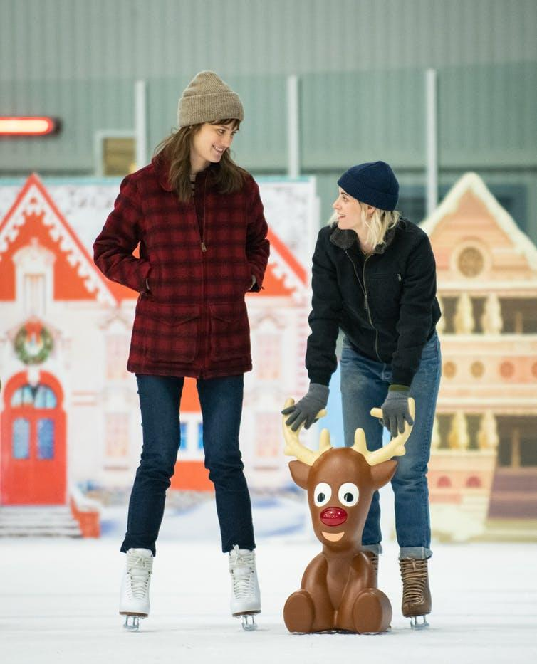 Two women ice skating with brown reindeer figurine