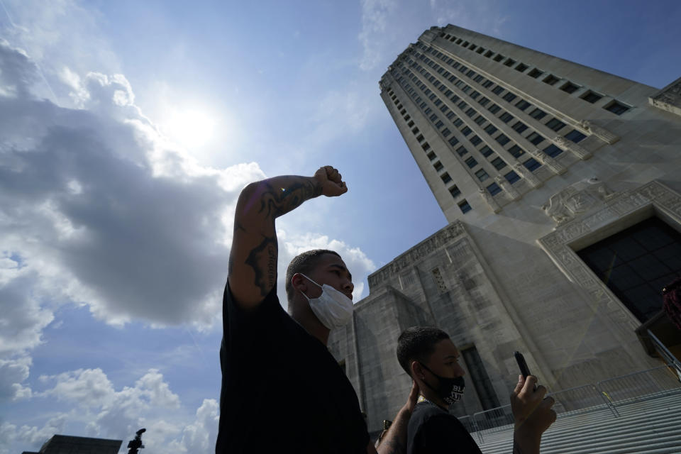 Devin Jackson, a student at Southern University, raises his fist during a rally, Thursday, May 27, 2021, in Baton Rouge, La., outside the state Capitol before a planned march to the Governor's mansion protesting the death of Ronald Greene, who died in the custody of Louisiana State Police. (AP Photo/Gerald Herbert)