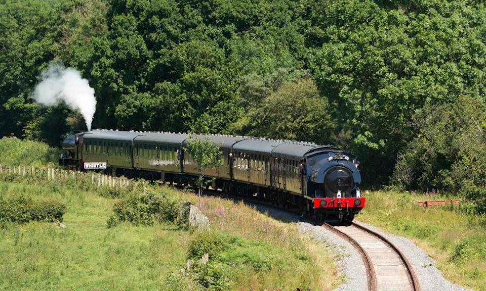 Steam train on track running through countryside