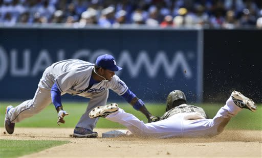 San Diego Padres' Logan Forsythe is tagged out by Los Angeles Dodgers shortstop Hanley Ramirez,left, while trying to steal second in the sixth inning of a baseball game in San Diego, Sunday, June 23, 2013. (AP Photo/Lenny Ignelzi)