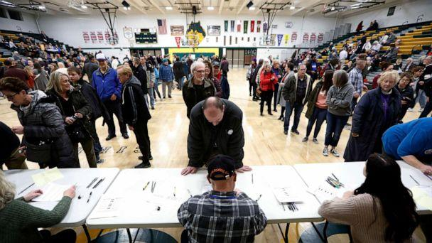 PHOTO: Local residents check-in after arriving at an Iowa Democratic caucus at Hoover High School, Feb. 3, 2020, in Des Moines, Iowa. (Charlie Neibergall/AP)