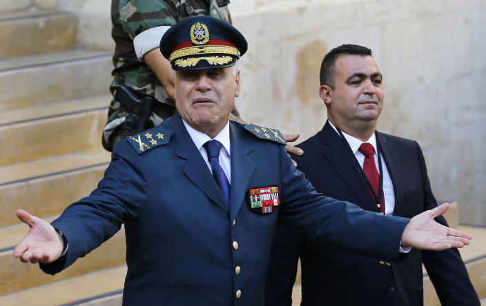 File - In this Oct. 31, 2016 file photo, Lebanese Army Commander Jean Kahwaji, left, reacts as he leaves the parliament building after he attended the session of the presidential elections, in Beirut, Lebanon. Lebanon's former army chief Jean Kahwaji told the lead investigator of last year's massive Beirut port blast on Thursday, Feb. 11, 2021, that he recommended years before the explosion that tons of seized ammonium nitrate stored there be sold privately or sent back to importer because the military had no use for them. (AP Photo/Hussein Malla)